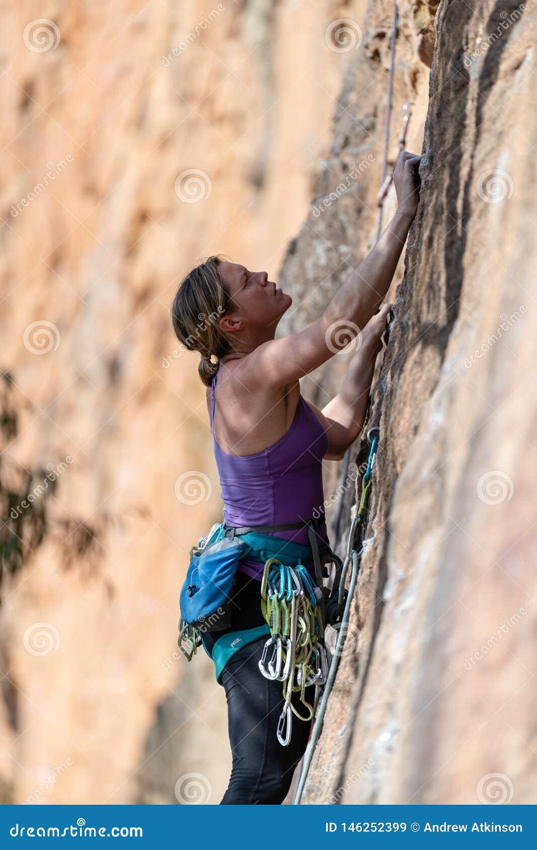 A rocha da mulher escala a cara vertical do penhasco no circuito de Ledge Porters Pass Centennial Glen das paredes no parque naci