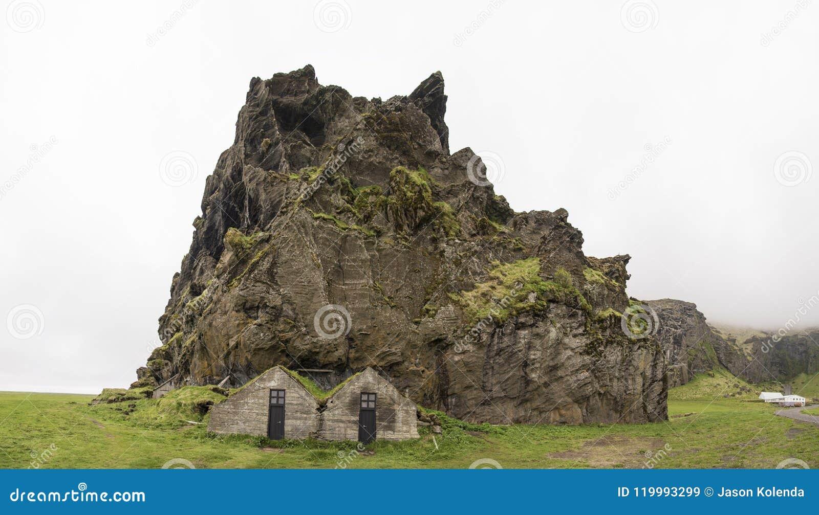 Rocha de Drangurinn com as casas islandêsas tradicionais, panorâmicos