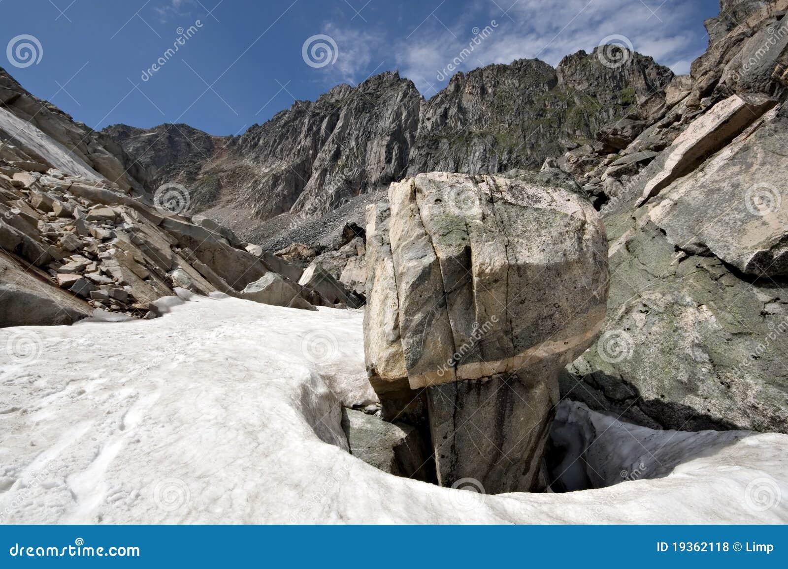 Rocha intricada entre a neve, montanhas de Sayan. Sibéria