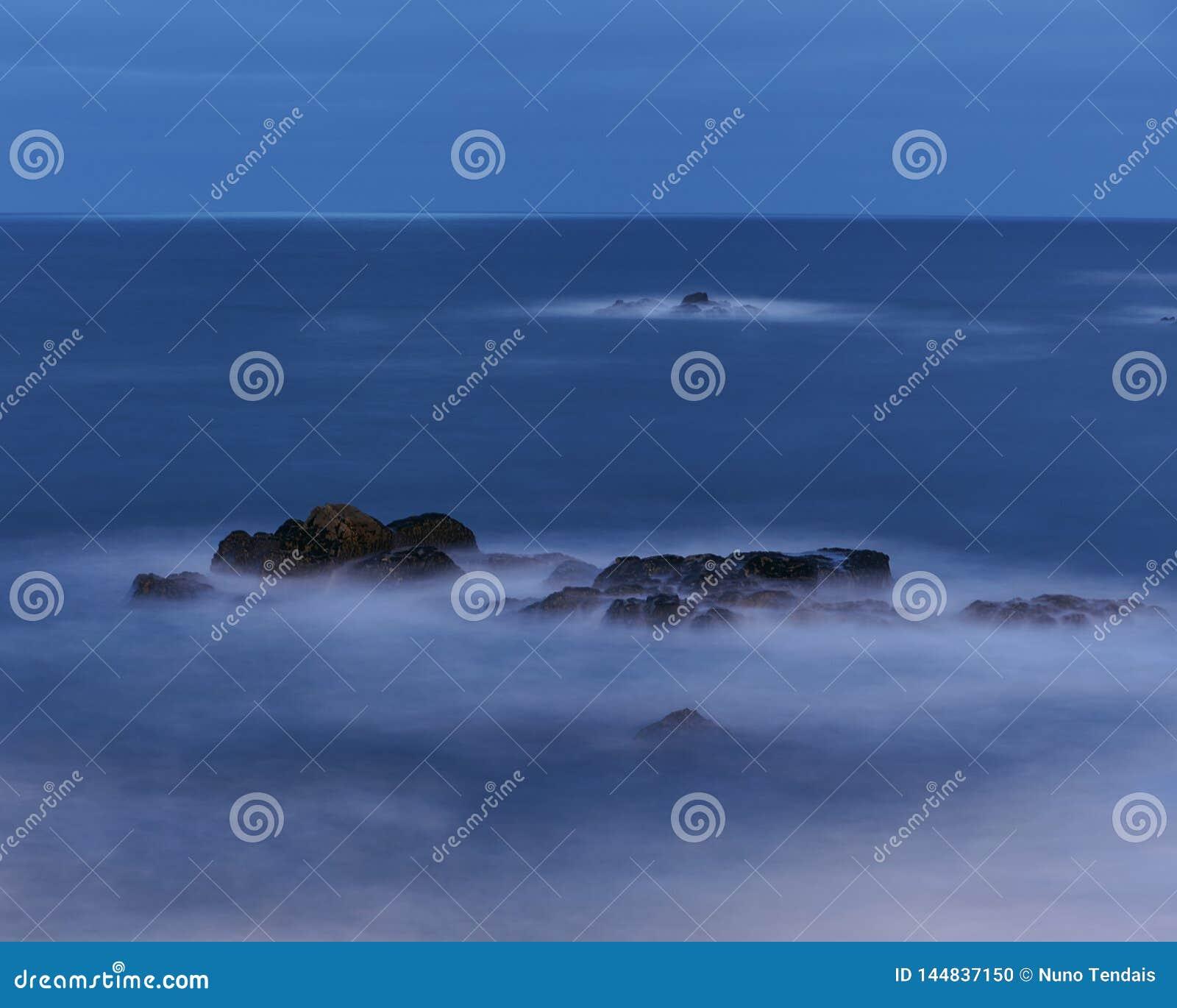 Rocha preta na hora azul no oceano Calmo, macio e frio