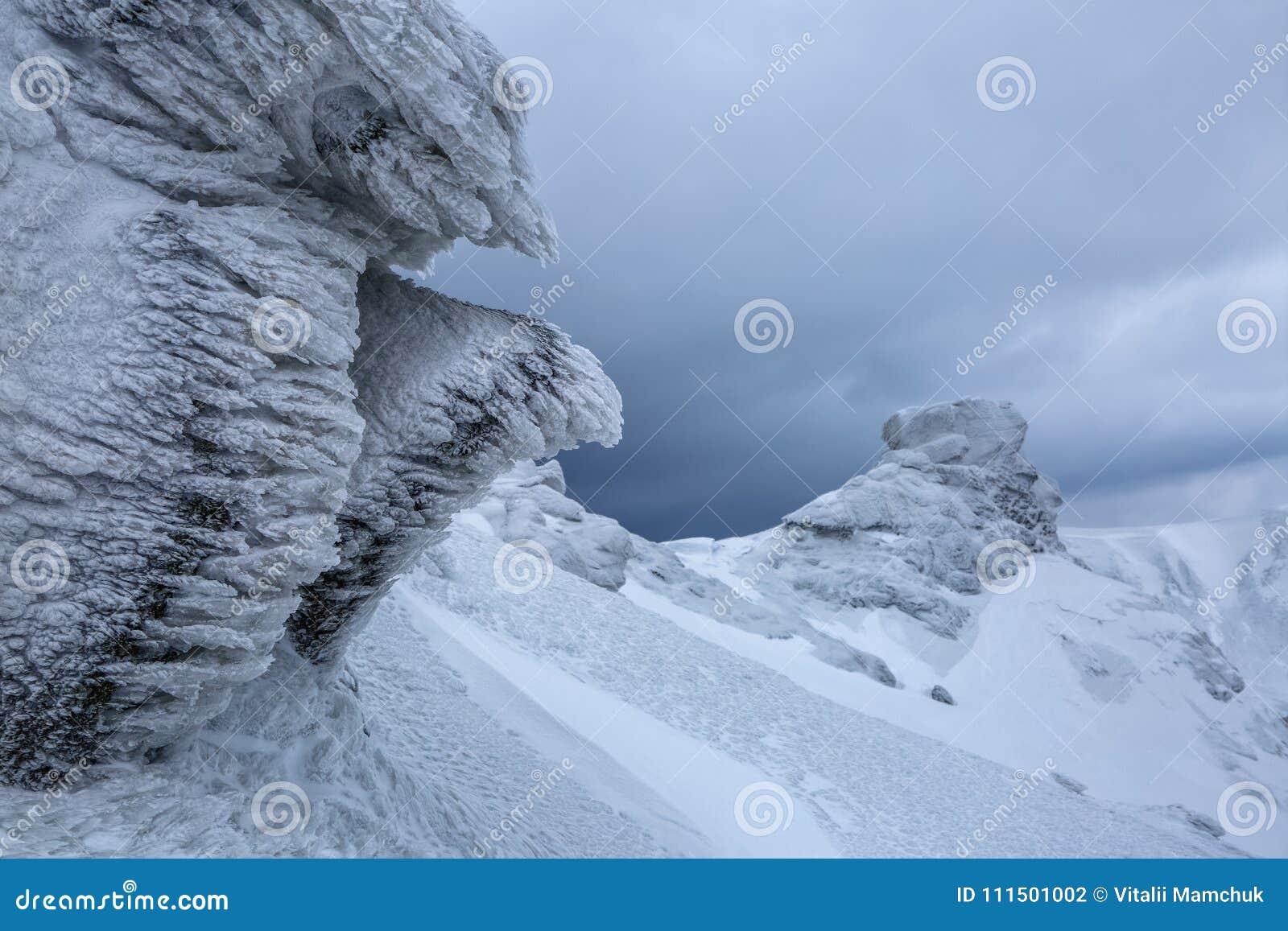 Rochas fantásticas misteriosas congeladas com gelo e neve de formulários e de estruturas estranhos dos contos de fadas Hora para