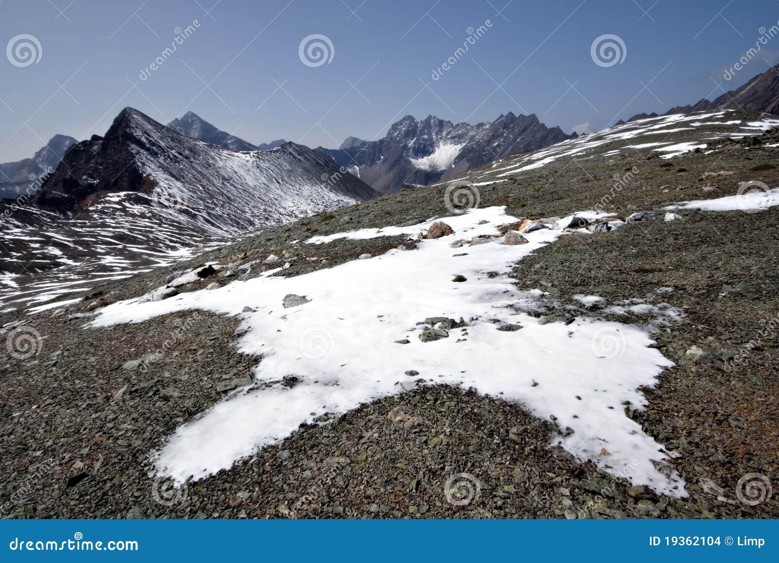 Rochas, neve, nuvens e céu em montanhas de Sayan. Sib