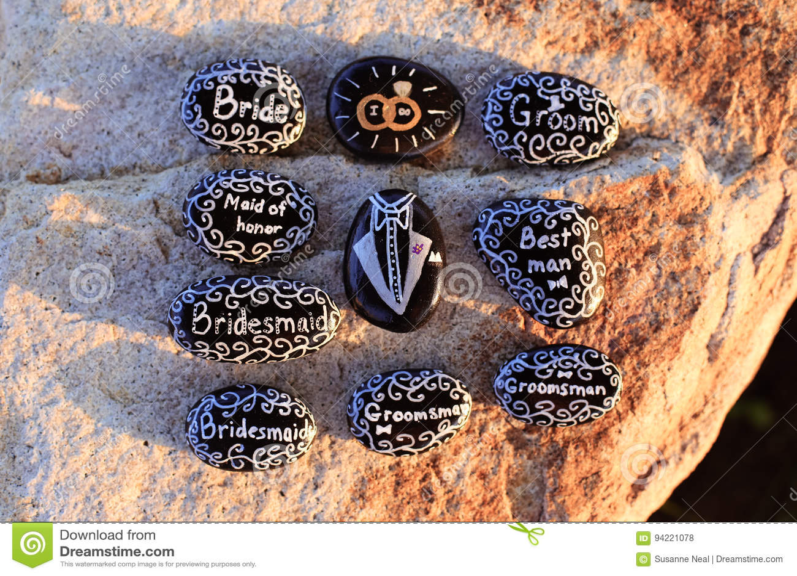 Roches peintes avec des mots nuptiales de partie dans le blanc sur les roches noires
