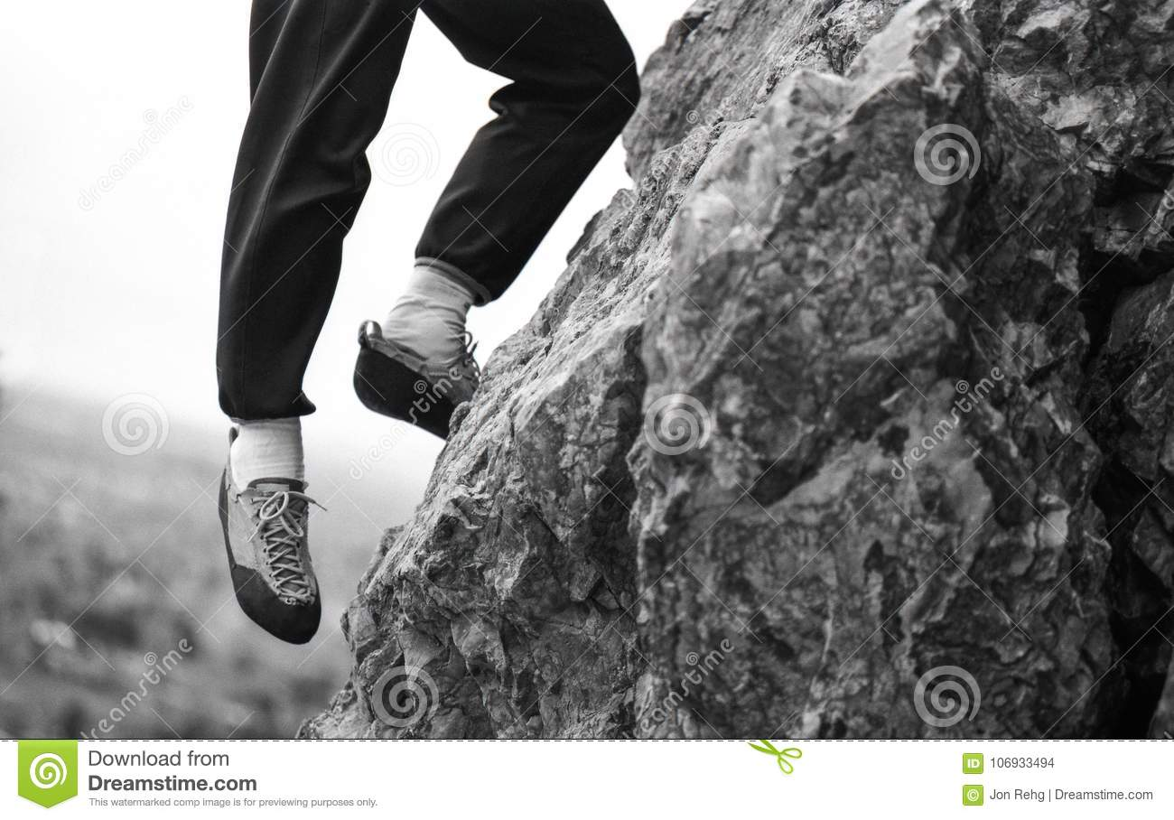 Rock Climber with One Foot Hanging Off Edge of Cliff Outcrop Over Looking Valley Below
