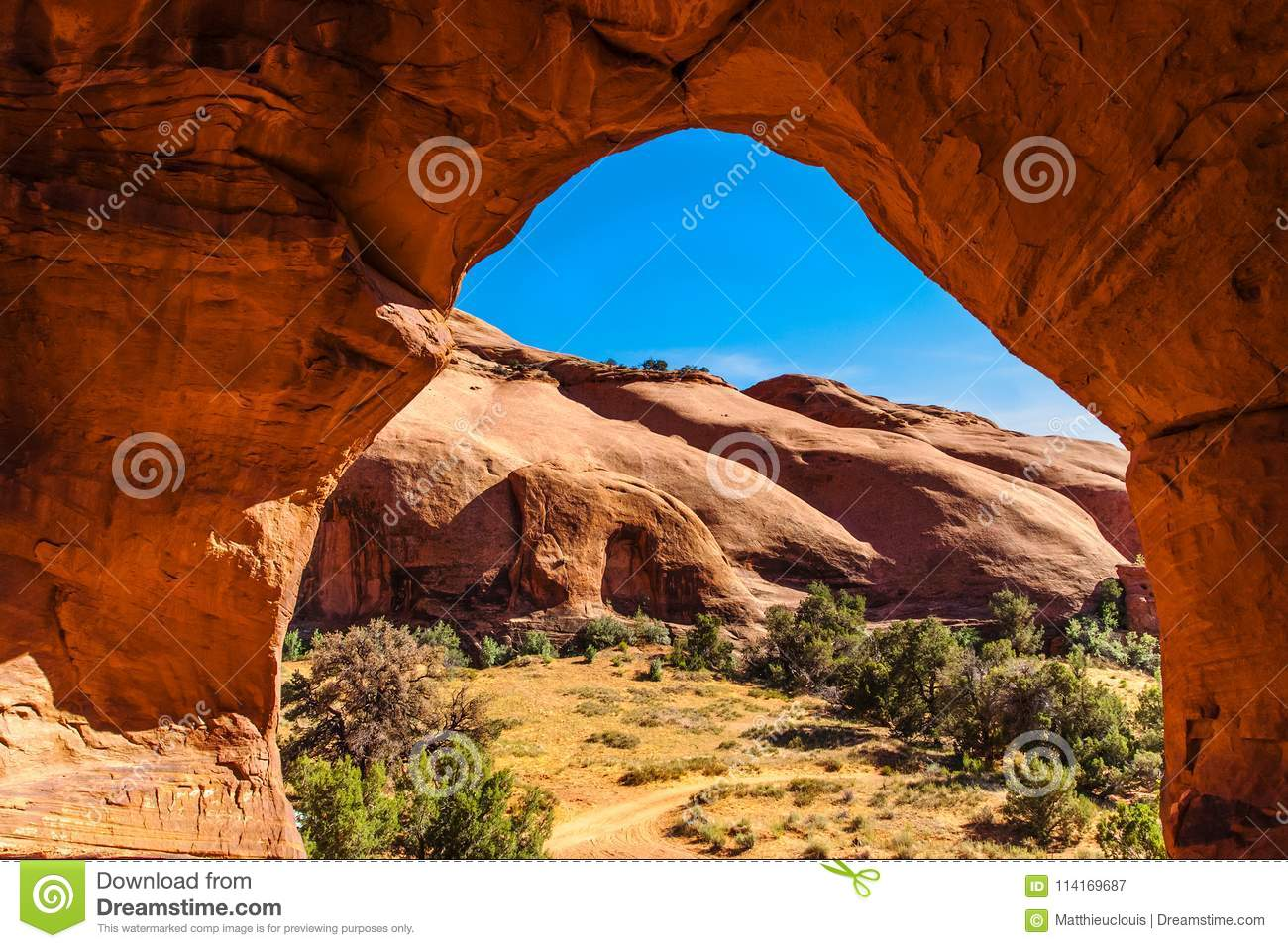 Rock formation and red cliffs framed through an arch in the Monument Valley Navajo Tribal Park