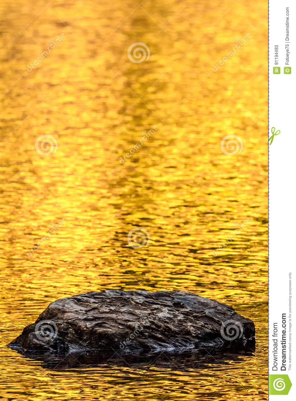 Rock and gold autumn lake reflections