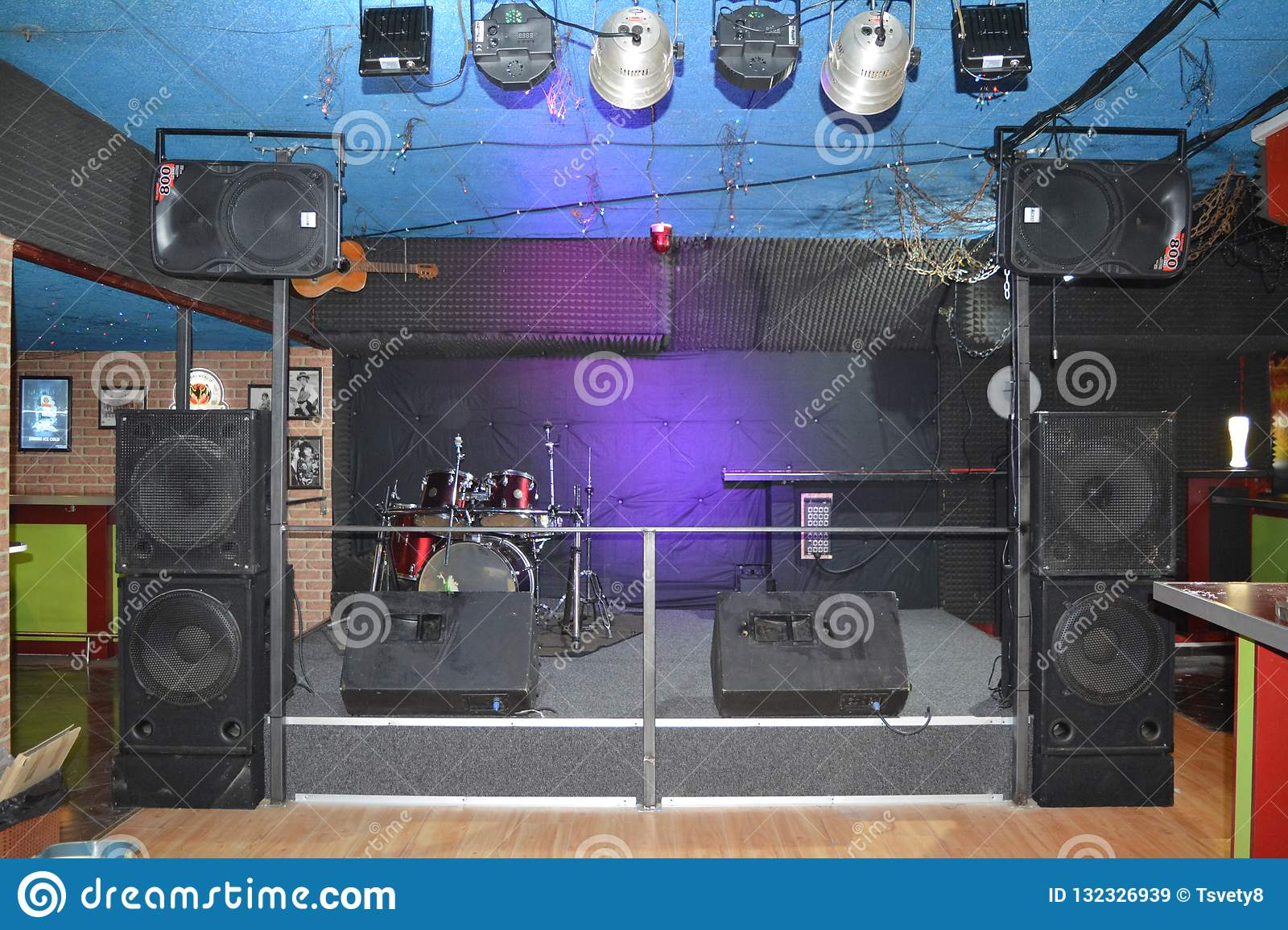 Rock stage for live music at a night club with lights and drums