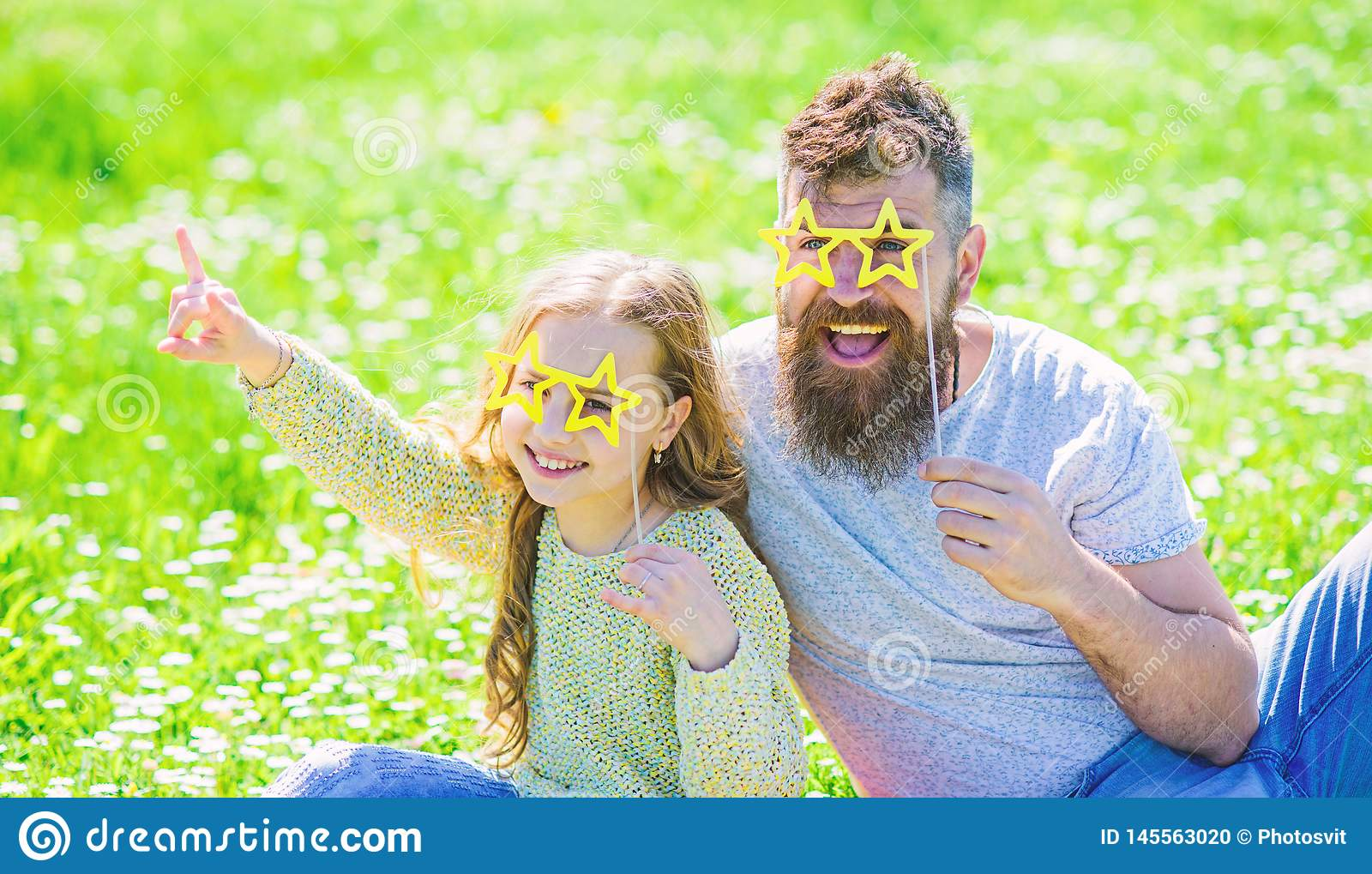 Rock star concept. Dad and daughter sits on grass at grassplot, green background. Family spend leisure outdoors. Child