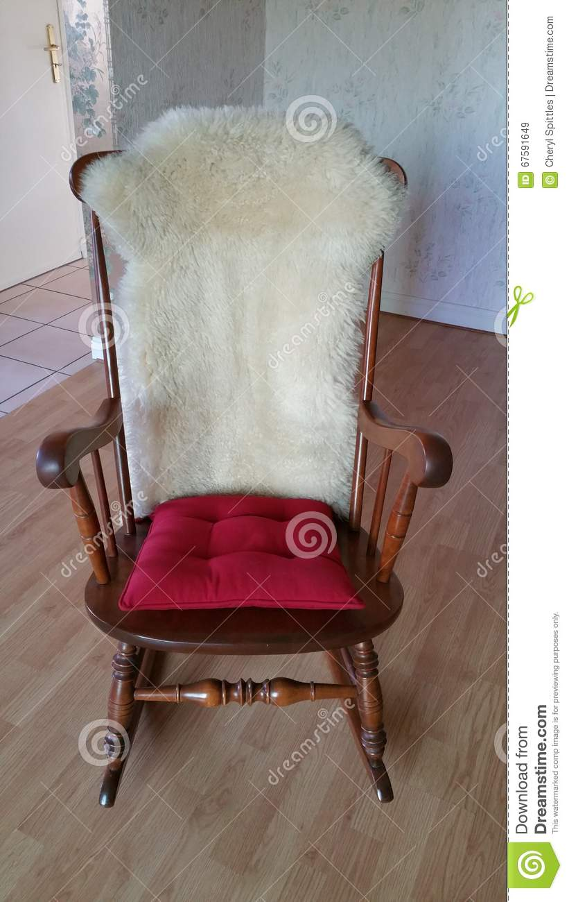 Rocking Chair With Red Cushion On Seat And Sheepskin On Chair Back