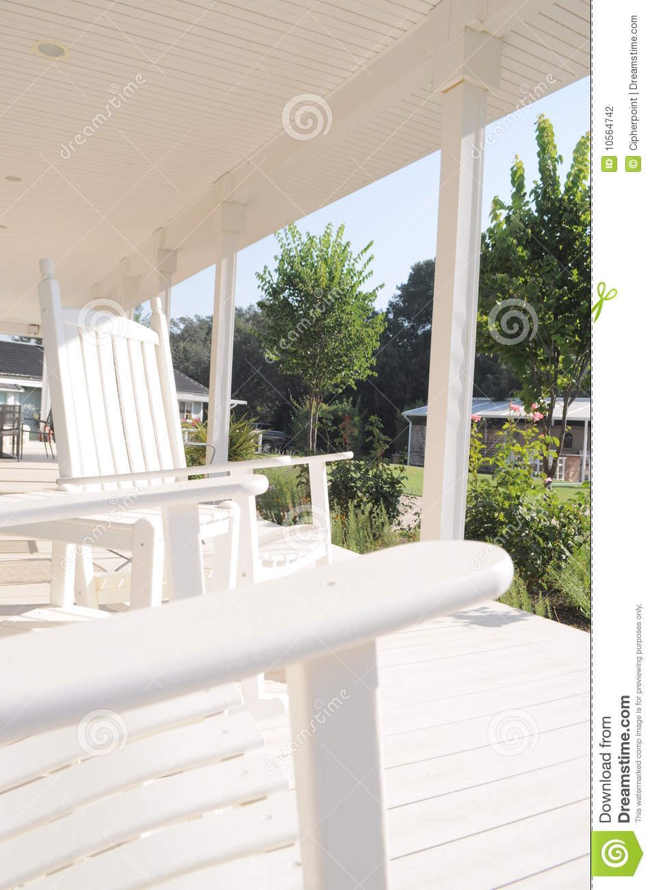 Rocking chairs on a white wrap around porch stock photo for Wrap around porch cost