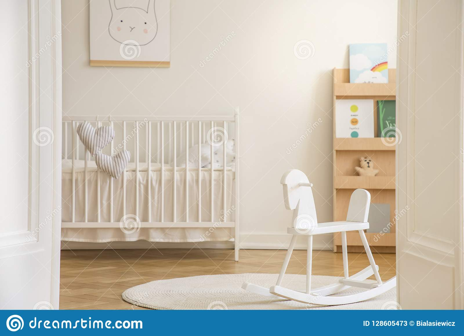 Rocking horse on rug in white kid`s bedroom interior with rabbit poster above cradle