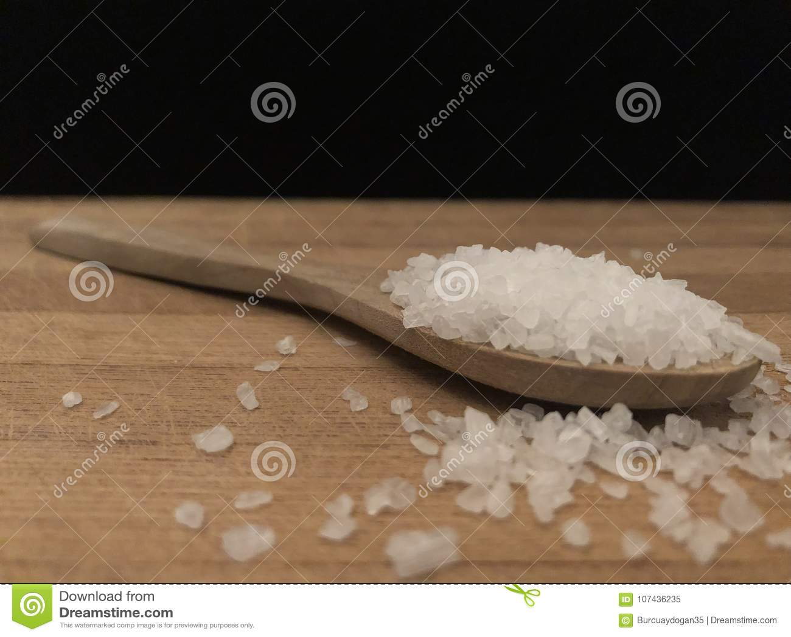 Rockowa sól w drewnianej łyżce na drewnianej tnącej desce z czarnym backboard