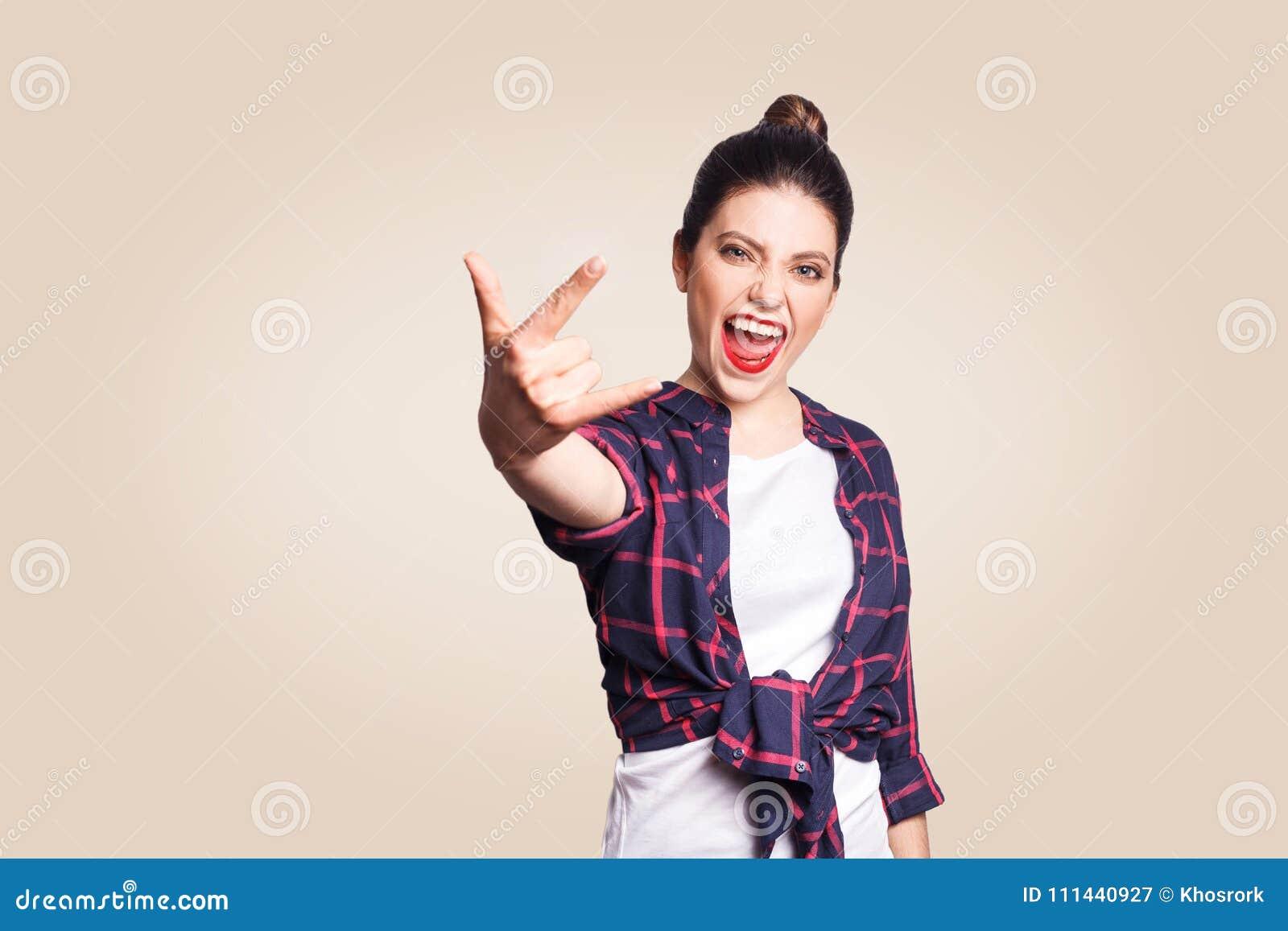Rockowy znak Szczęśliwy śmieszny toothy smiley młodej kobiety seansu skały znak z palcami Studio strzelający na beżowym tle