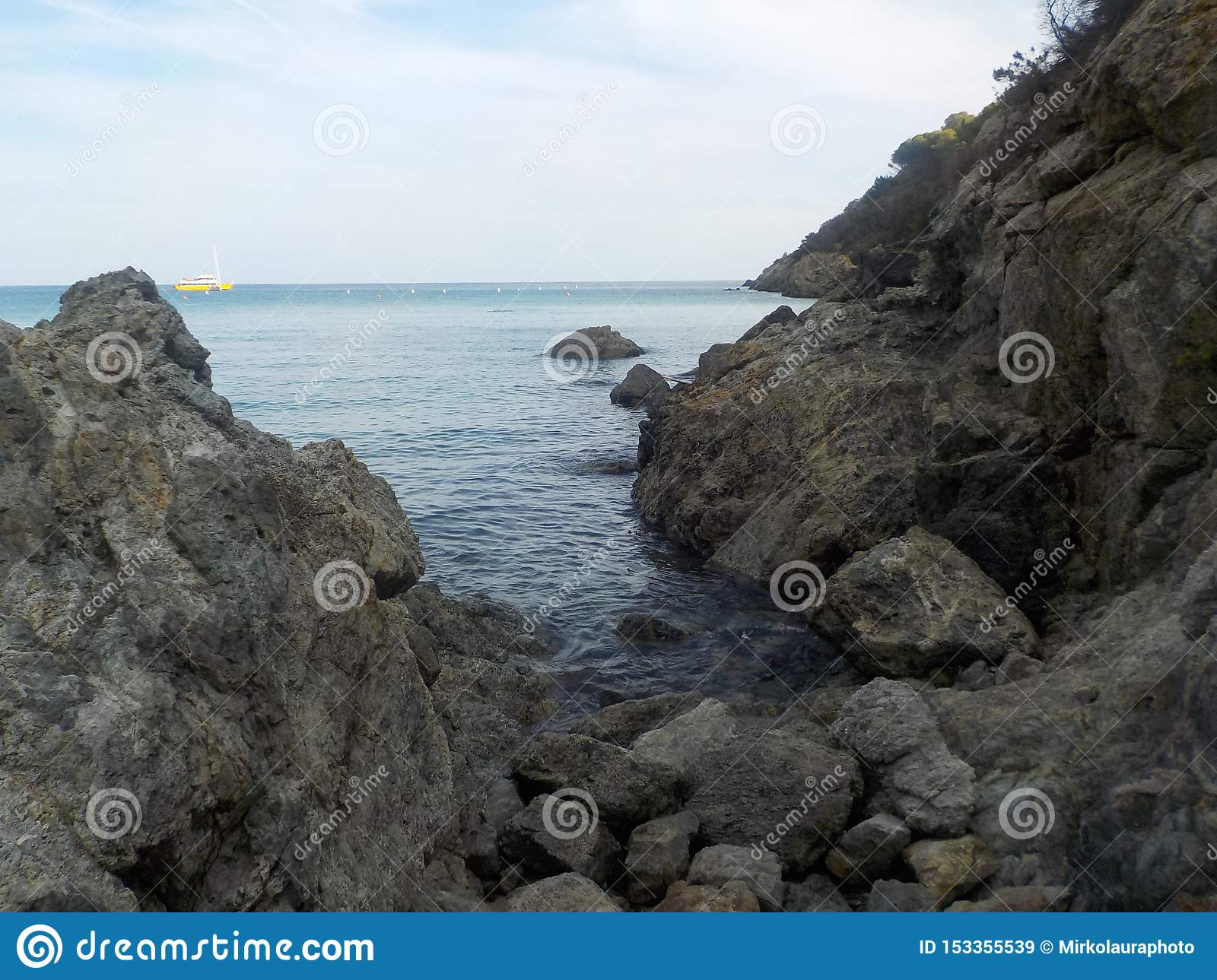 Rocks and blue sea with a distant yellow boat