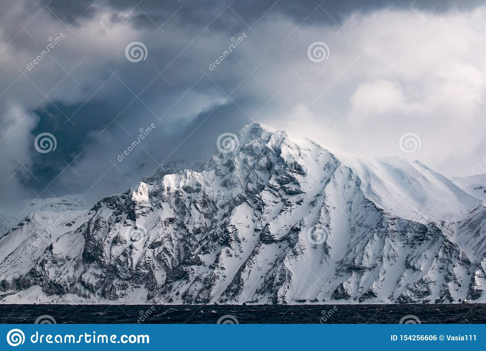 Rocky coast of one of the Kuril Islands in the winter during a snow storm