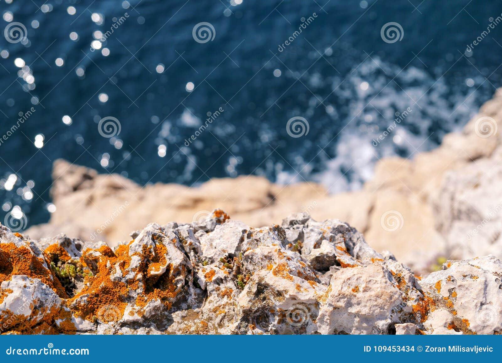 Rocks at seashore of Adriatic sea, Mediterranean, closeup. Aerial top view of sea waves hitting rocks on the beach.