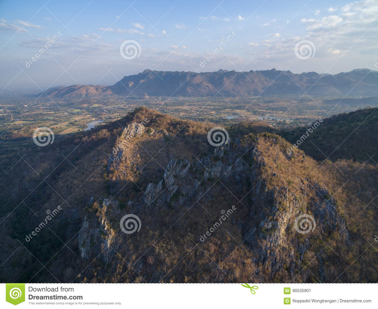 Rocky cliff and mountain range with highland and houses background