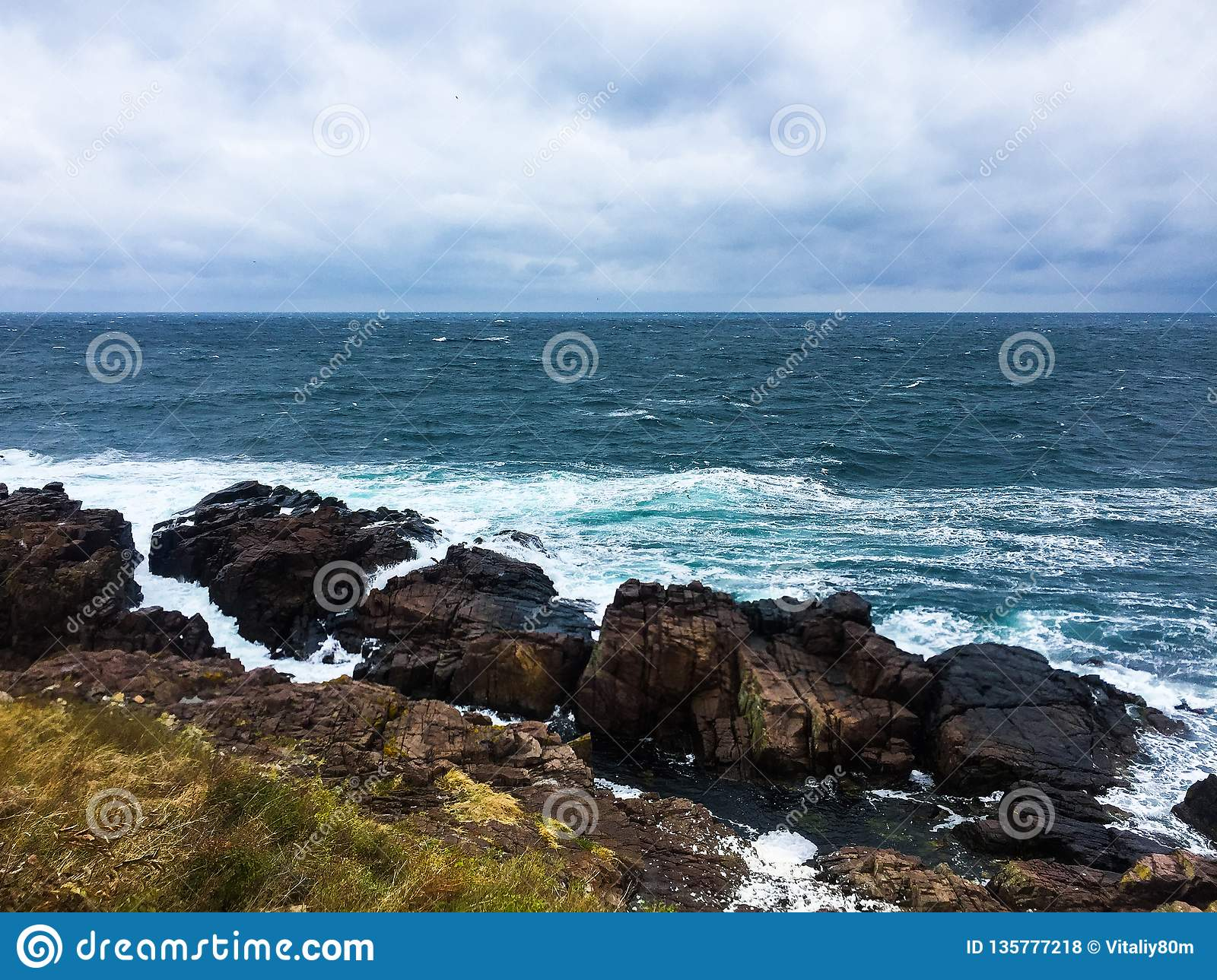 Rocky seashore. Cloudy windy weather.