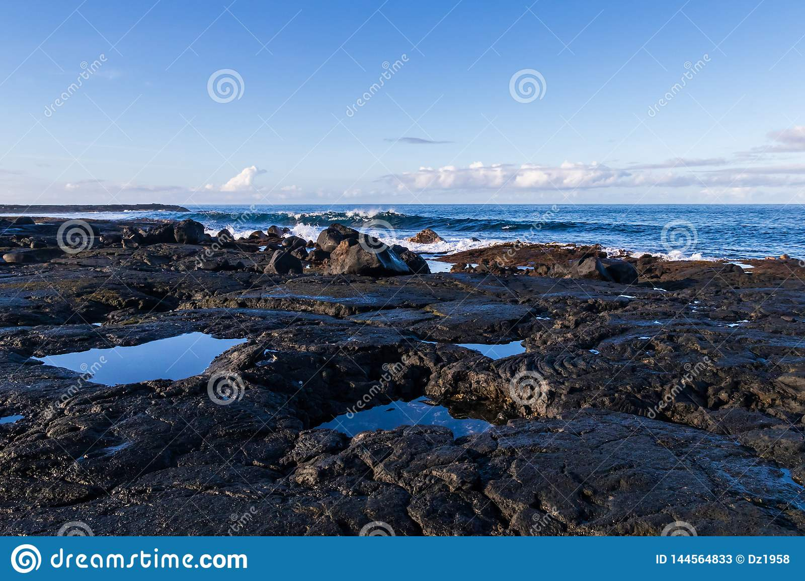 Rocky volcanic shoreline in Hawaii. Low tide; pools of water in rock cavities. Waves, ocean blue sky and clouds in background.