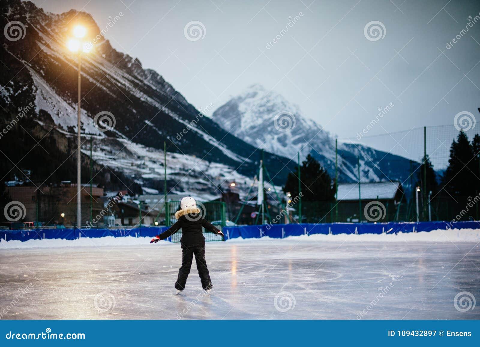 9 roczniak dziewczyny łyżew na lodzie w wieczór na illuminat