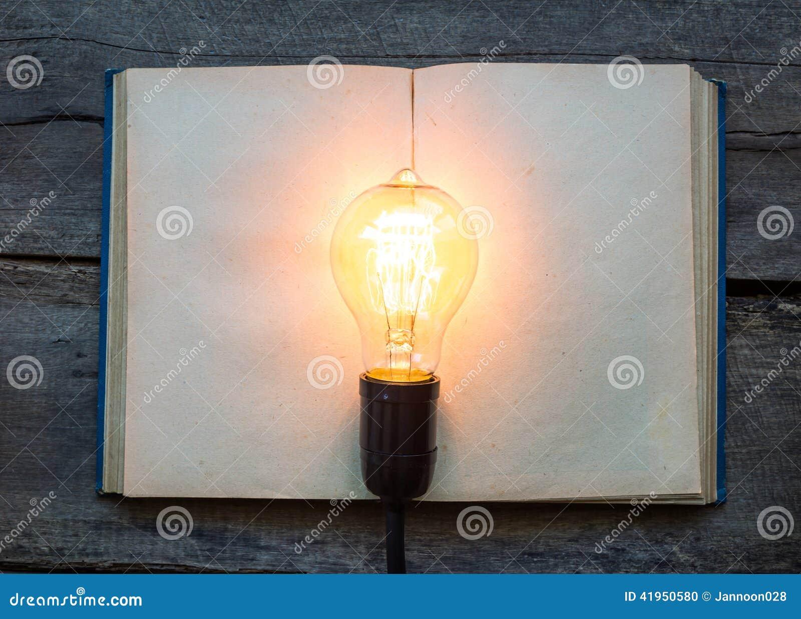 Rocznik żarówka na drewno stole i książka