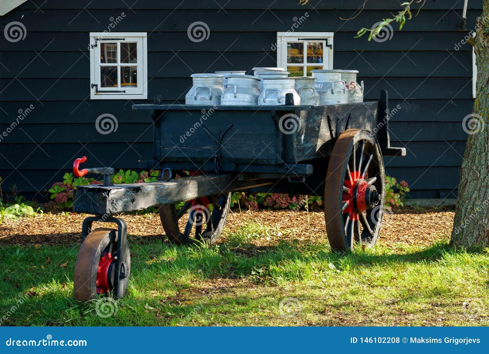 Rocznik fura z nabiału mleka puszkami przed tradycyjnym starym drewnianym domem