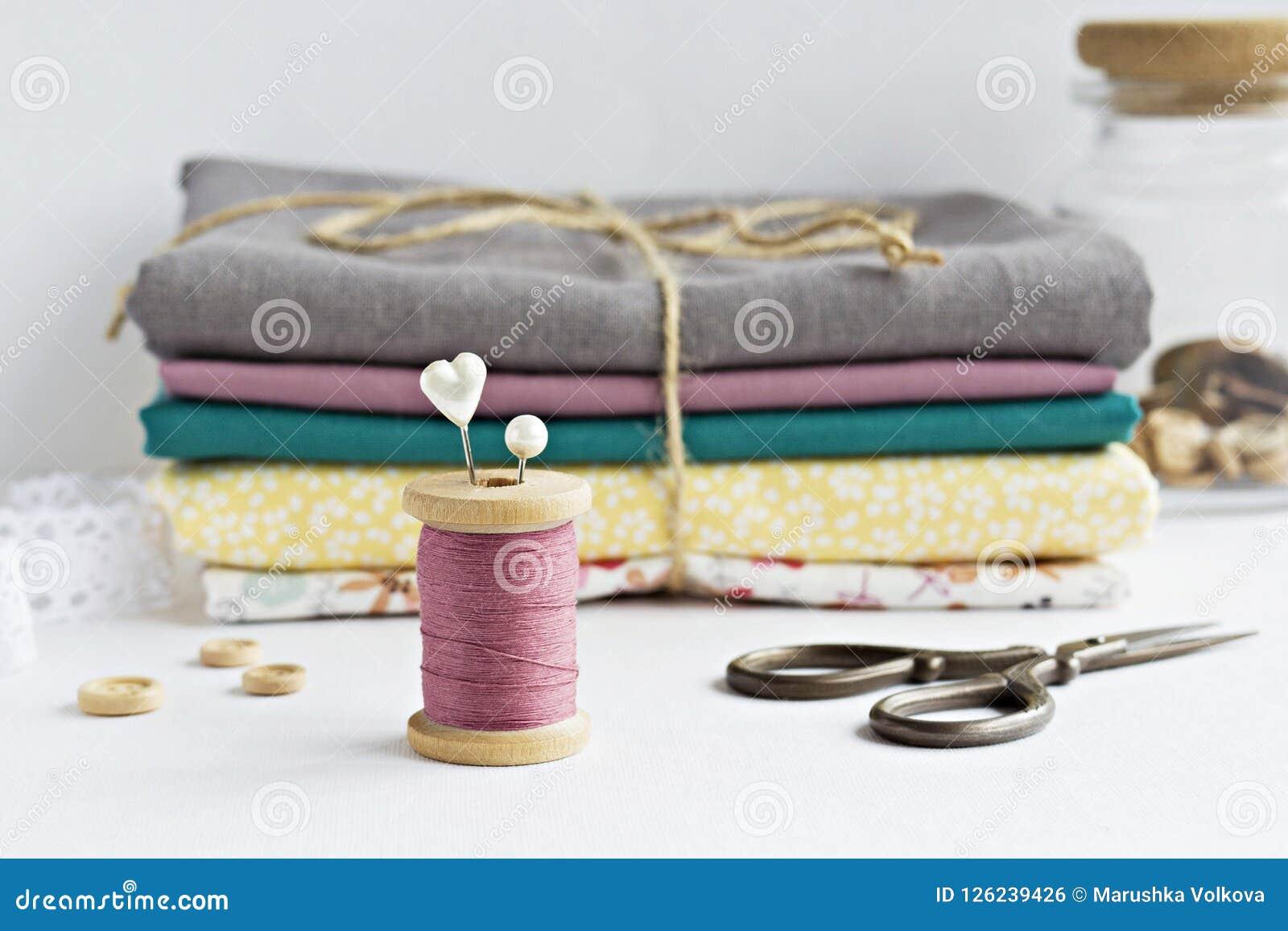 Rocznik niciana cewa, szpilki, drewniani guziki, nożyce i tkaniny,