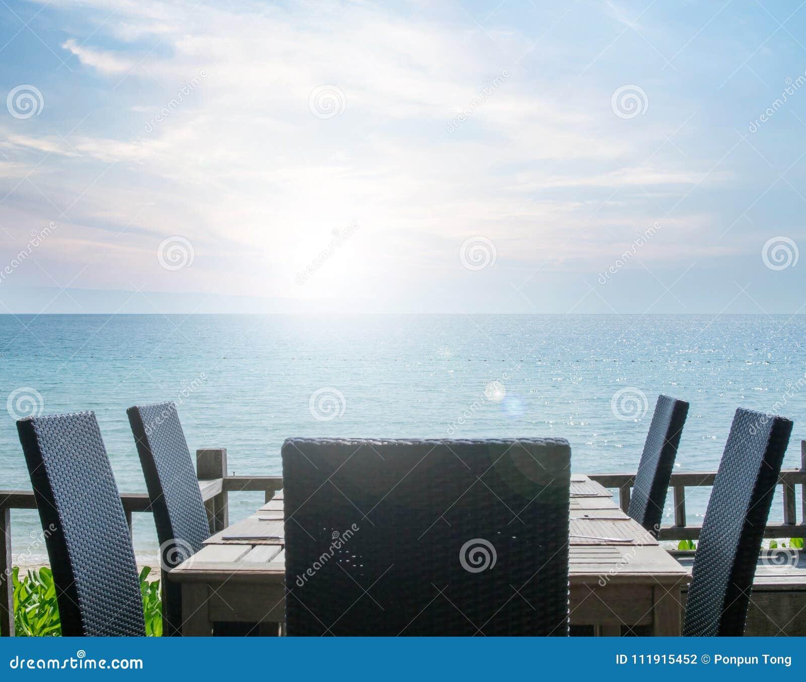 Rocznik wykonujący na stołowym położeniu przy plażową restauracją z dennym widokiem,