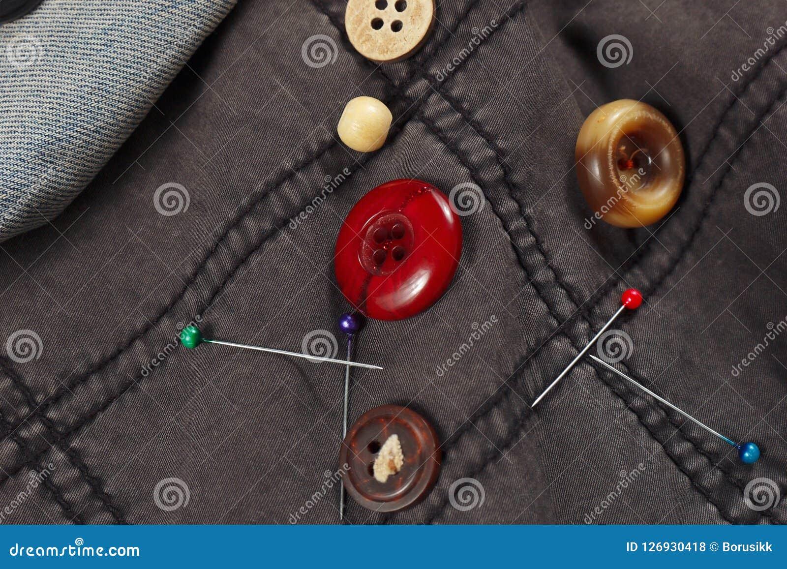 Rocznik zapina i szpilki na czarnej bawełnie i błękitnym drelichowym zbliżeniu