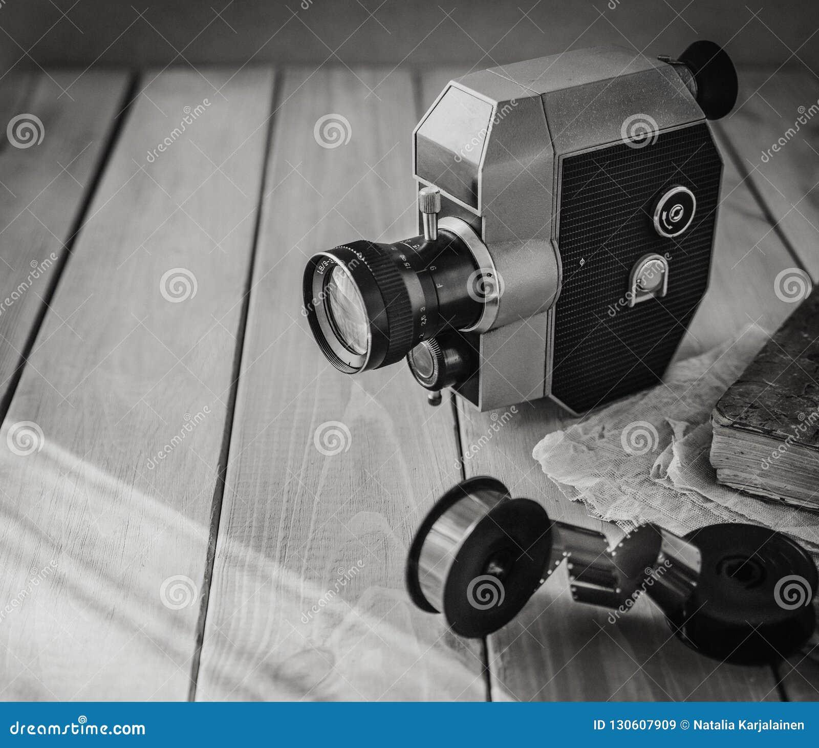 Rocznika filmu stara kamera i ekranowe rolki na drewnianym stole, stara książka, clothl fotografia retro kosmos kopii