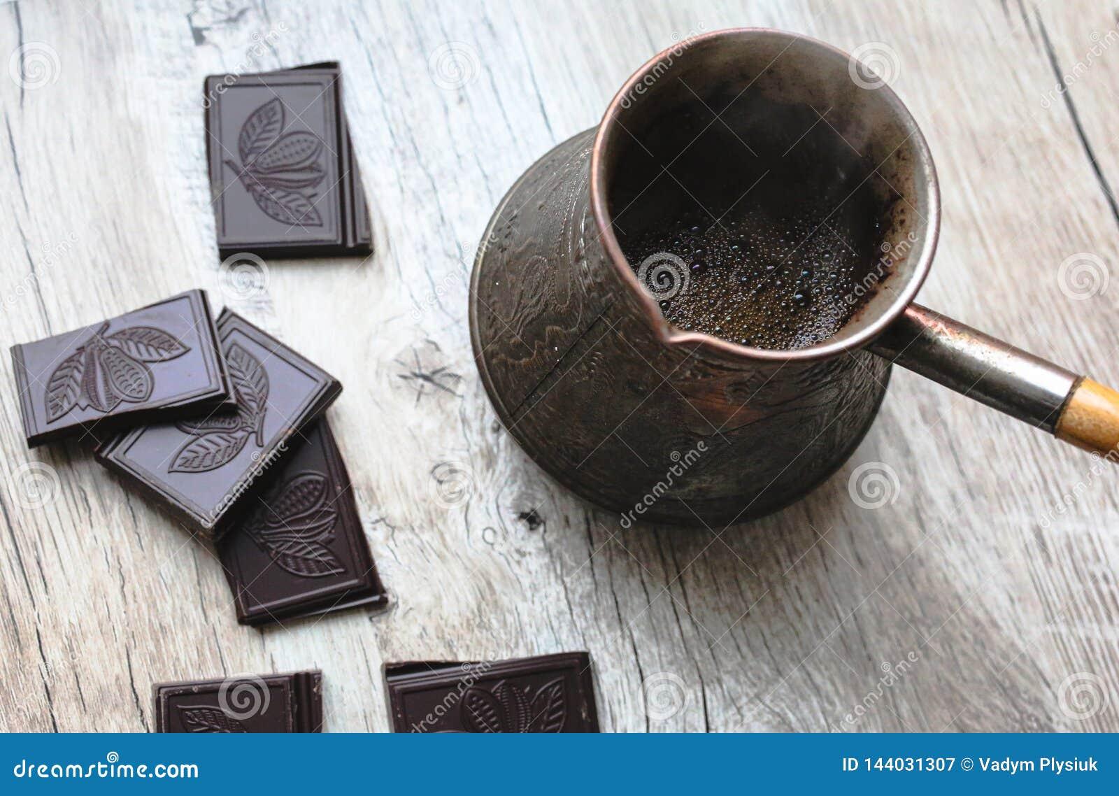 Rocznika jezve z świeżo warzącą kawą Czarna czekolada z cacao fasolami śpiewa na drewnianym tle Tureckiej kawy garnek