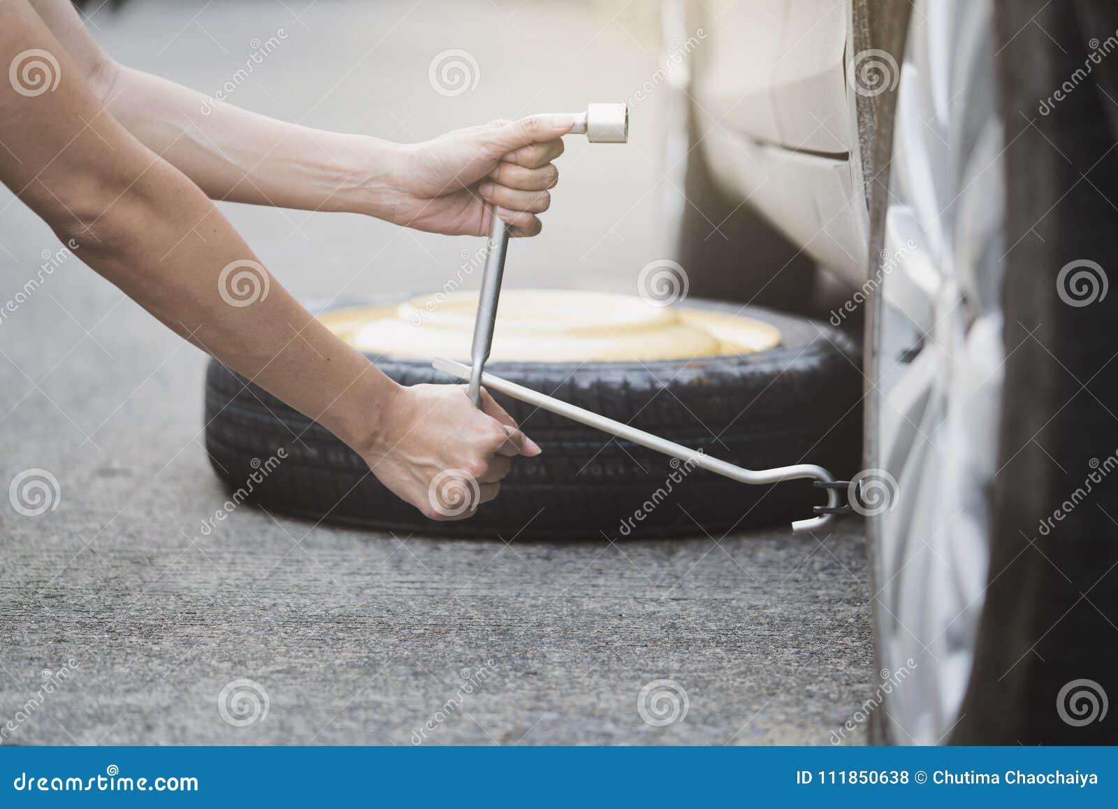 Roda de mudança da mulher em uma borda da estrada