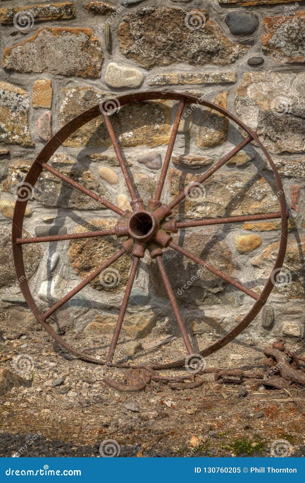 Roda oxidada do carro que descansa contra uma parede de pedra não 2