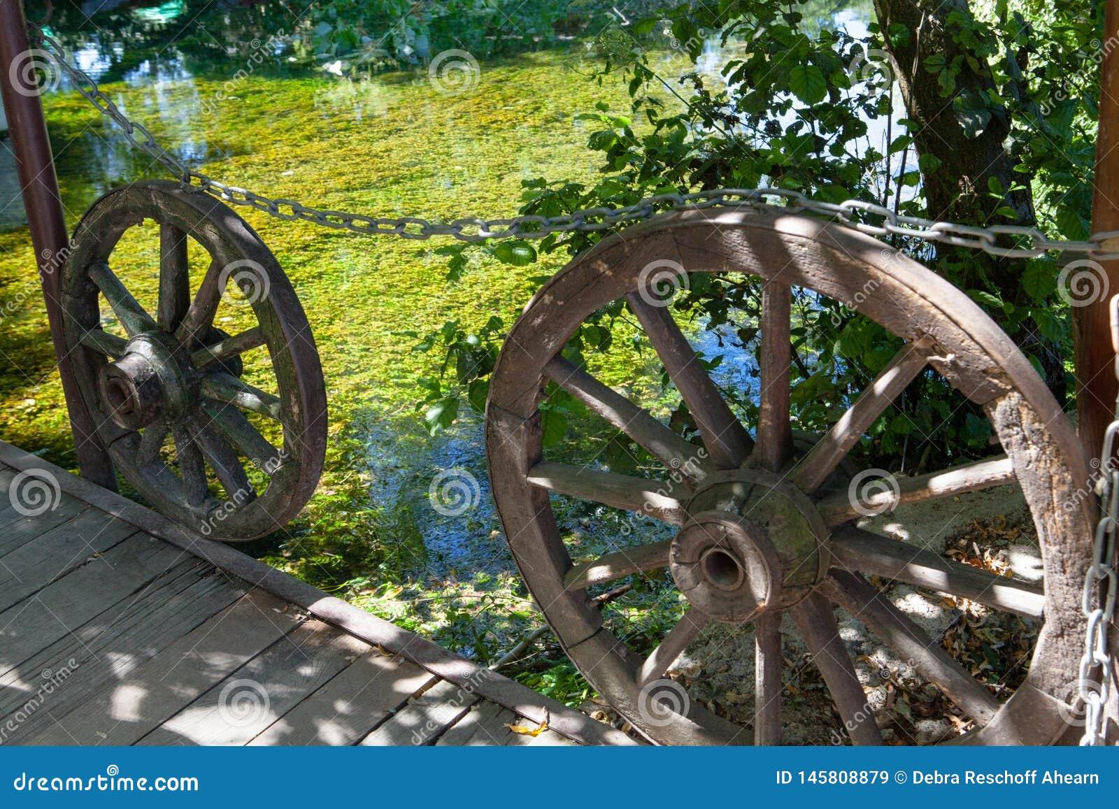 Rodas de vagão de madeira velhas ao lado do lago