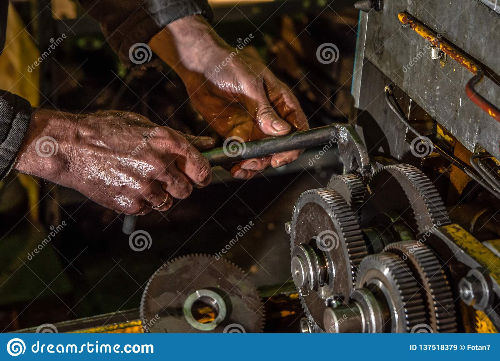 Rodas do metal da engrenagem com mãos do trabalhador no close-up industrial da máquina