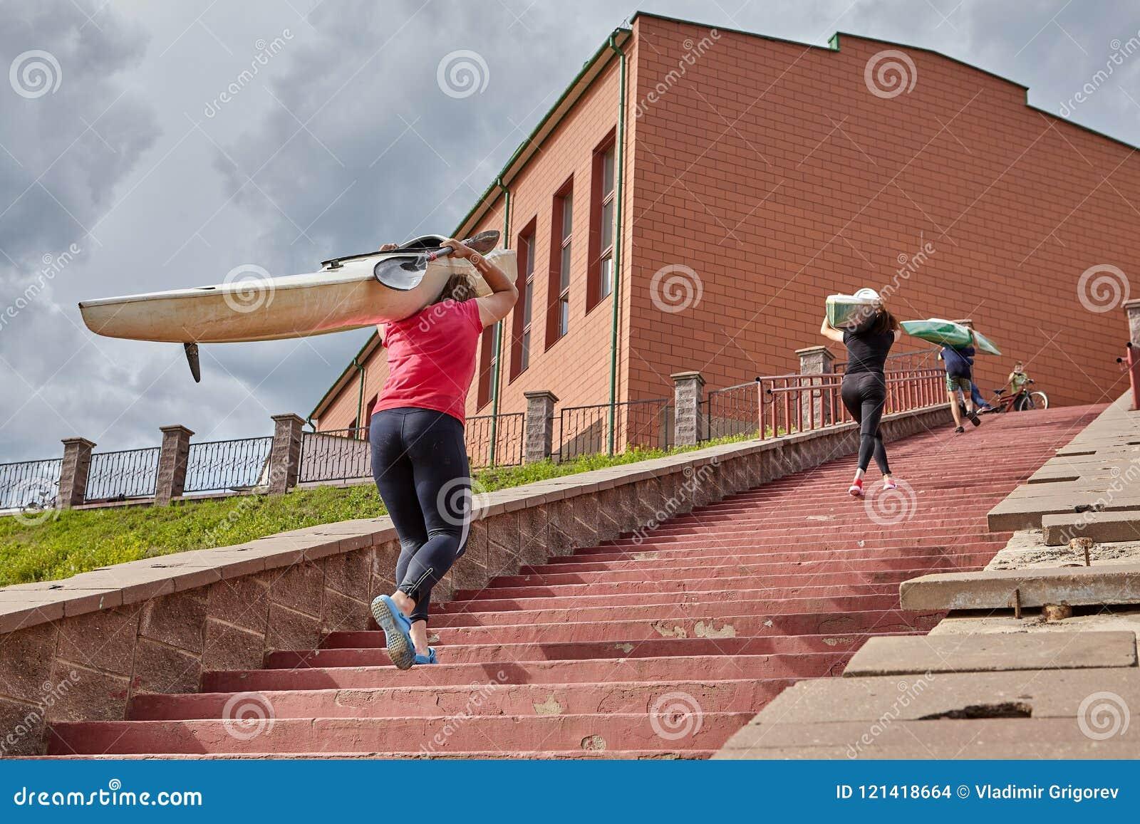 Roddare går uppför trappan med kanoten på skuldror, når de har rott drevet