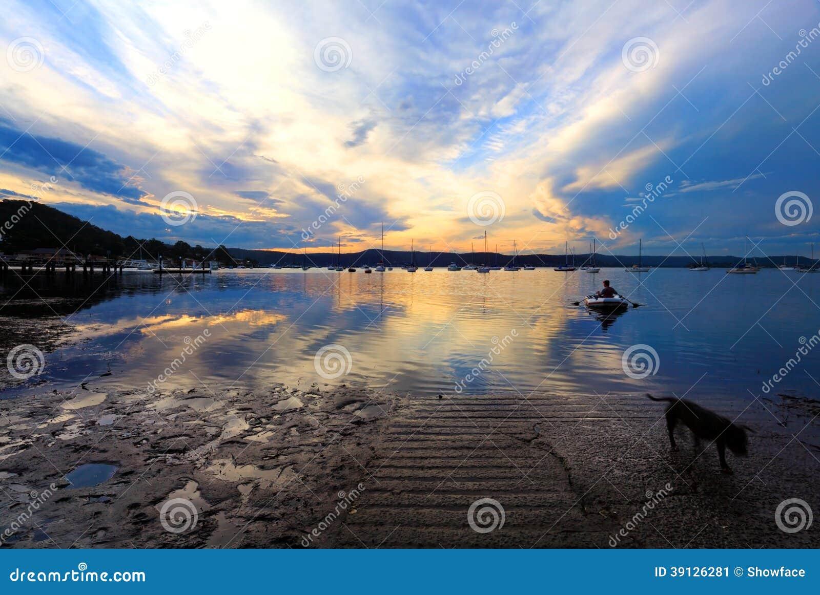 Roddbåt som kommer att stötta i solnedgång för sen eftermiddag