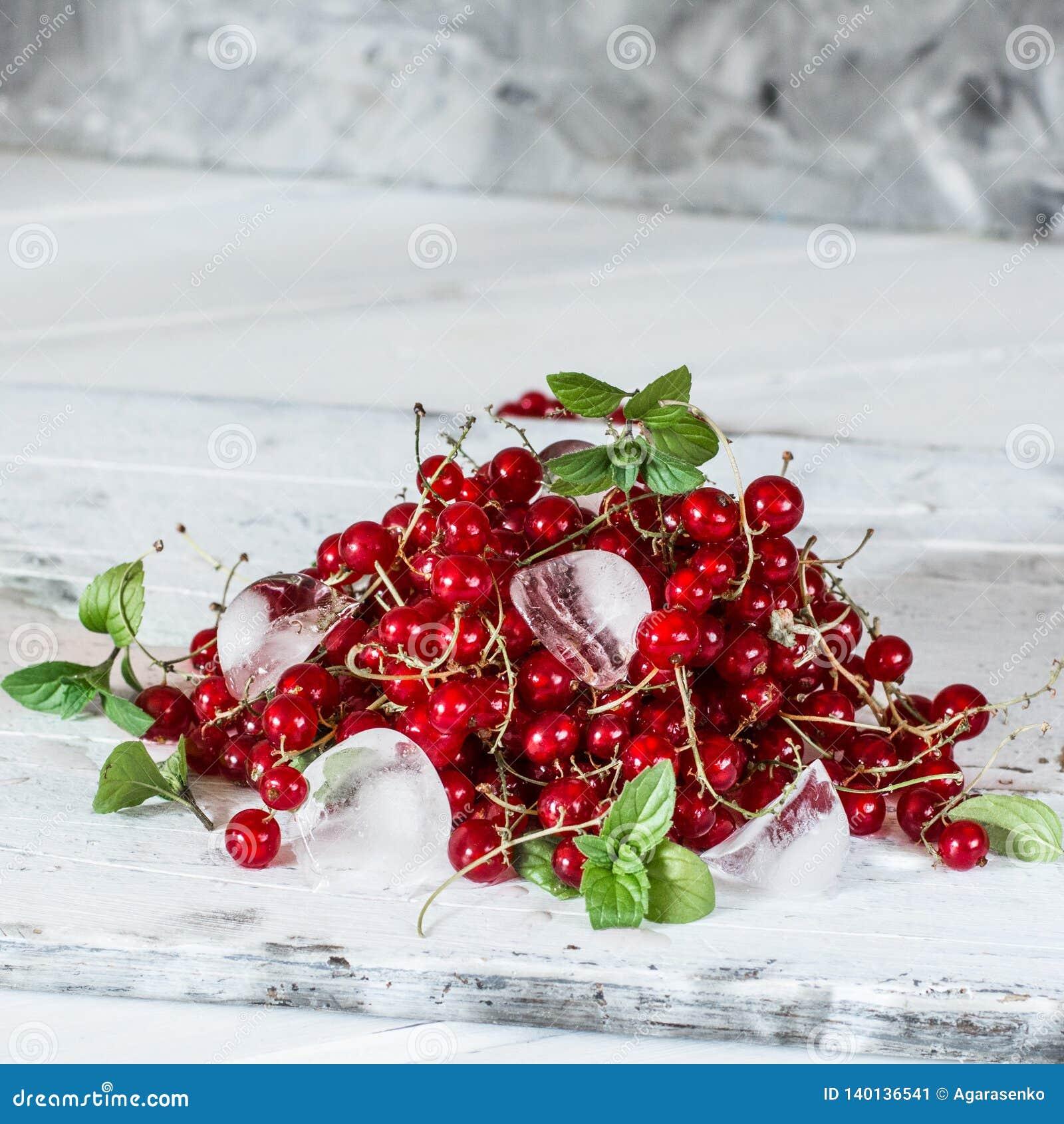 Rode aalbes met ijs en groene bladeren op witte houten achtergrond stilleven van voedsel Kubussen van ijs met bessen