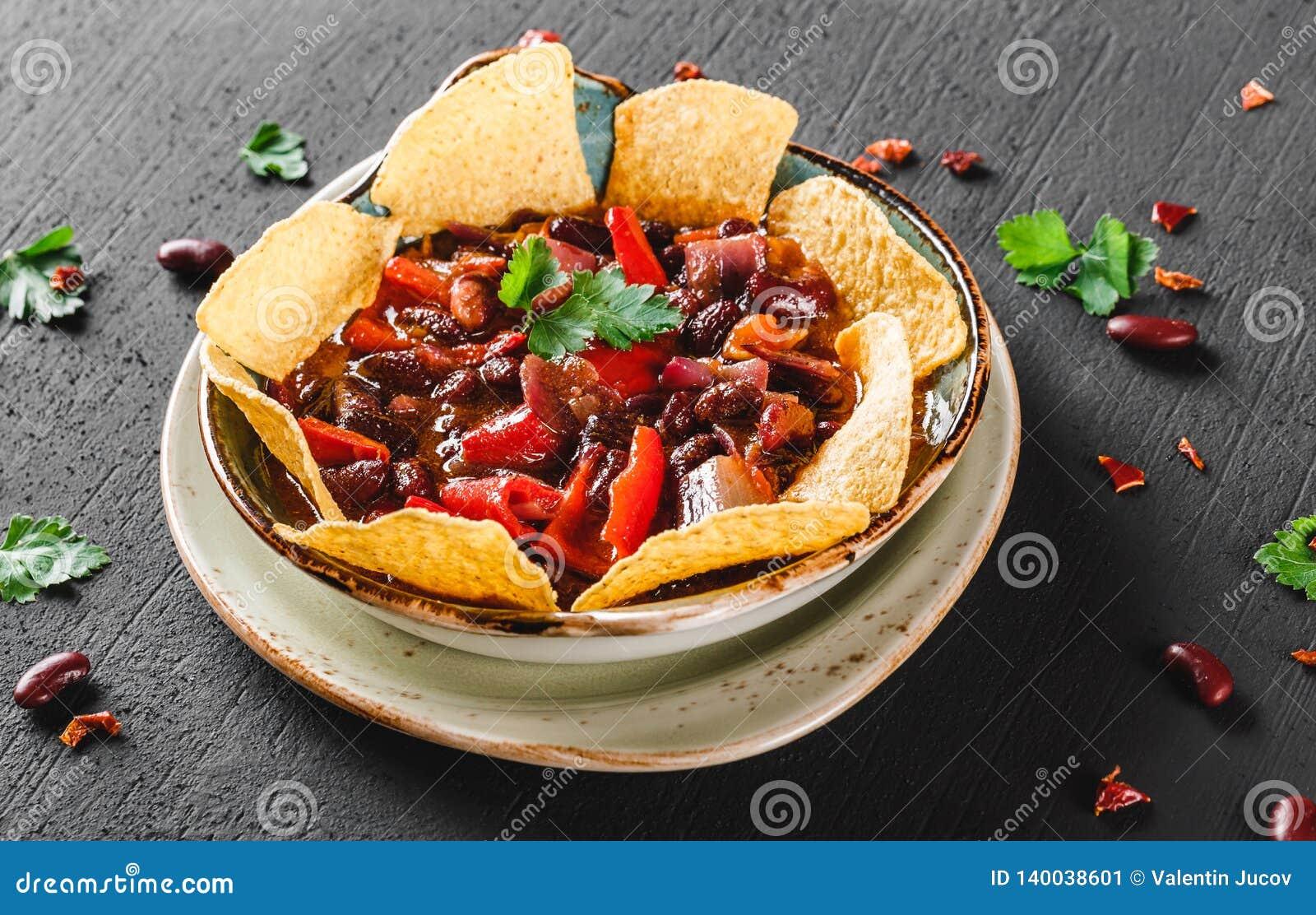 Rode boon met nachos of pitabroodjespaanders, peper en greens op plaat over donkere achtergrond Mexicaanse snack, Vegetarisch voe