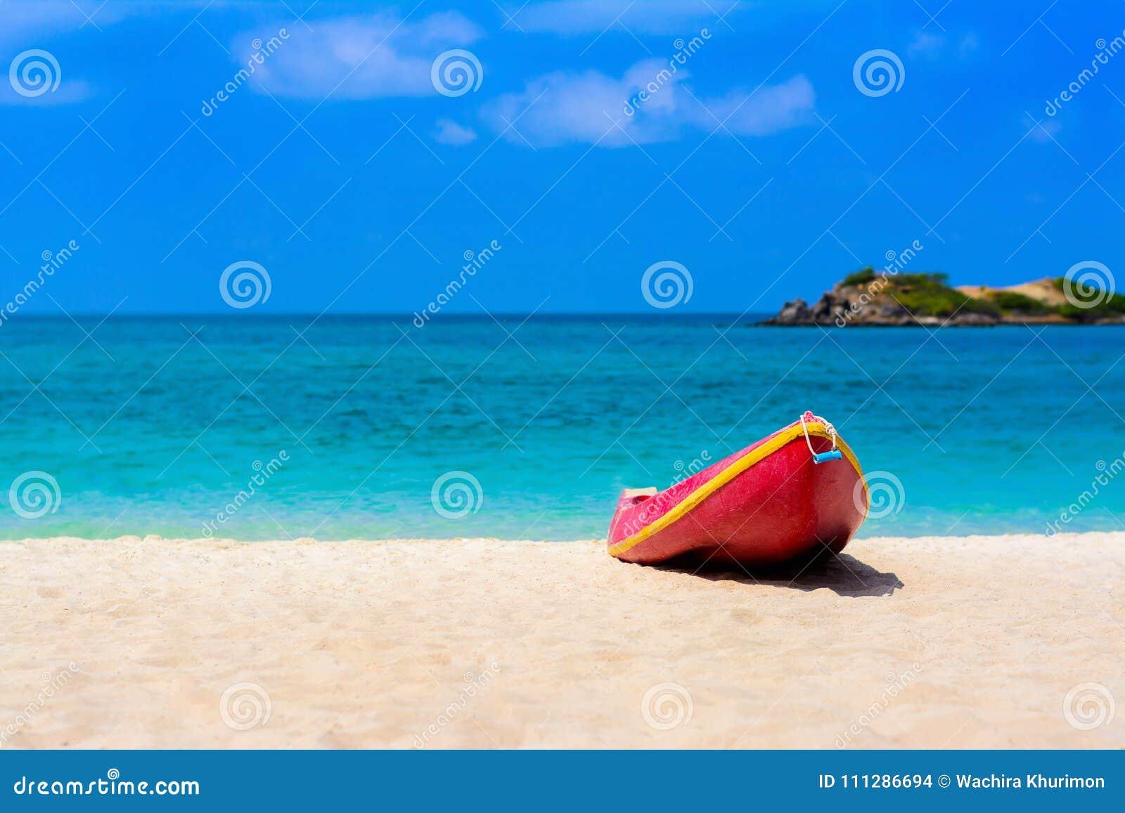 Rode boot op het strand met blauwe overzees en blauwe hemel