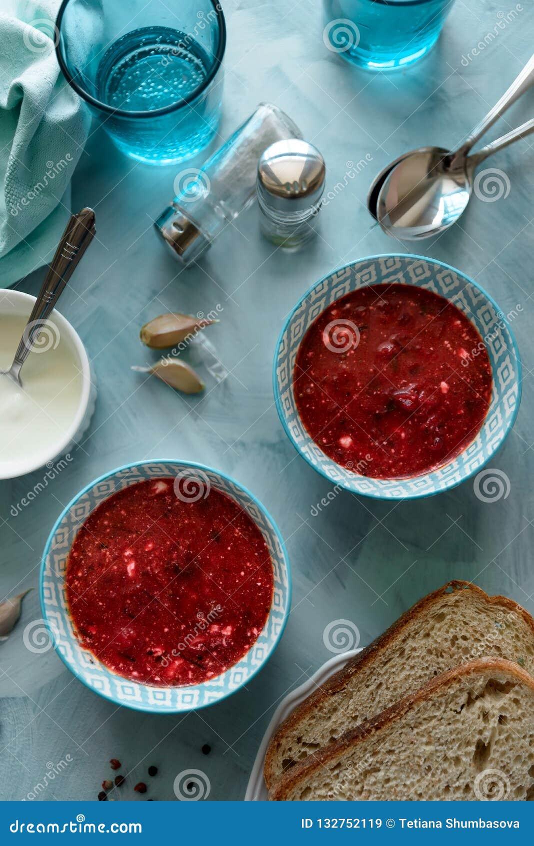 Rode borschtsoep in blauwe kom met zure room, brood, knoflook en kruiden op blauwe houten achtergrond Hoogste mening Vlak leg