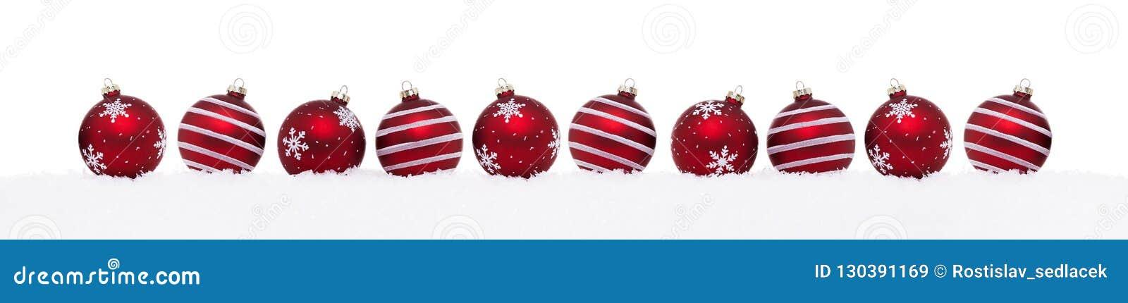 Rode die Kerstmisballen op een rij op sneeuw worden geïsoleerd