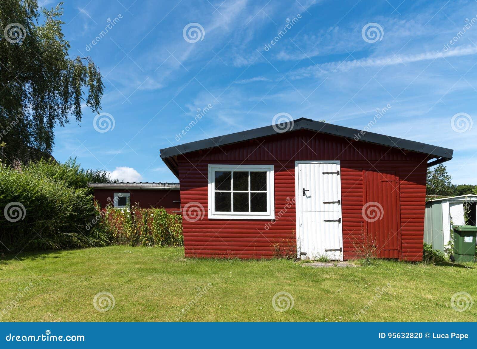 Rode die tuin met witte deur op een zonnige dag wordt afgeworpen