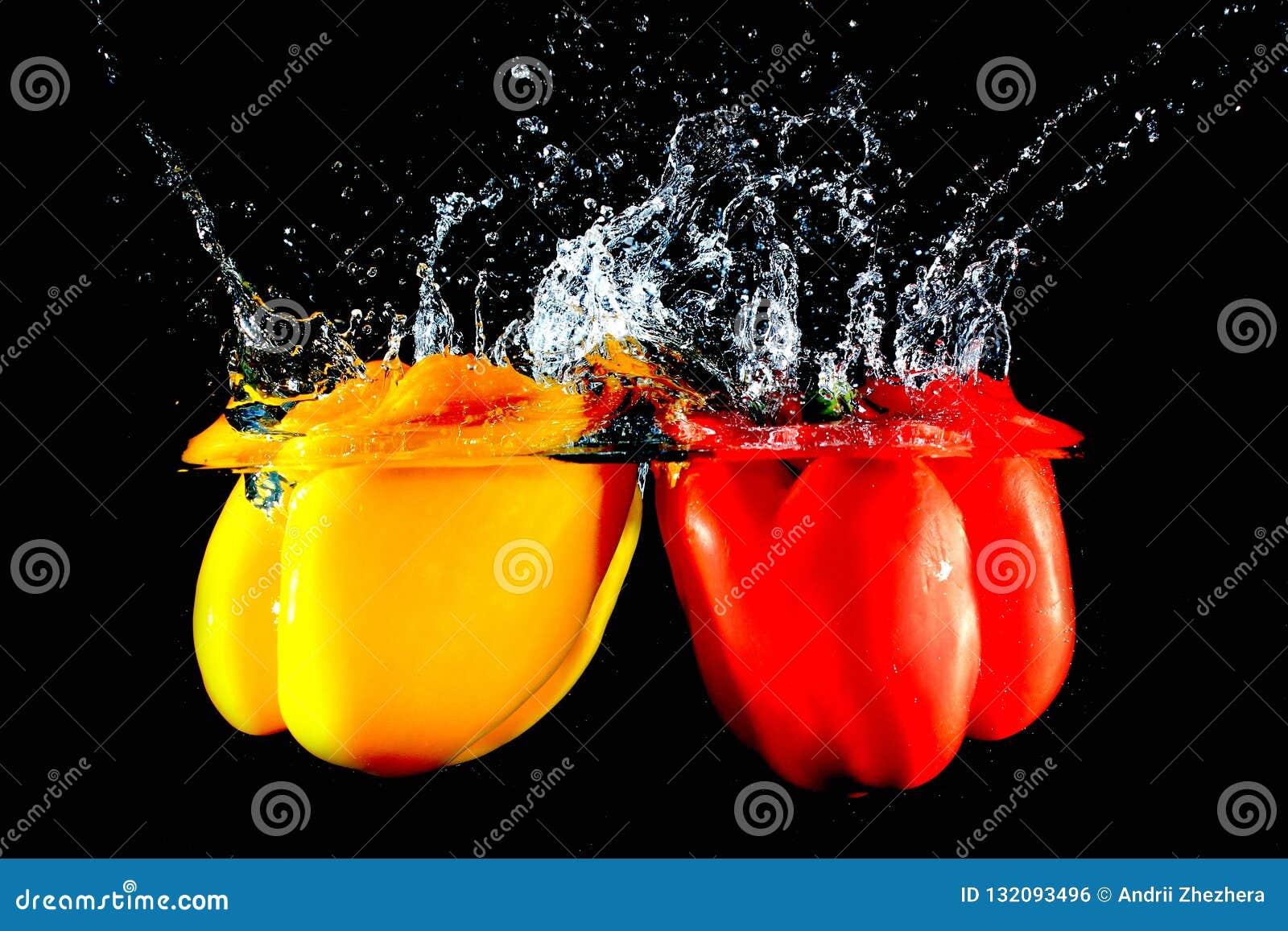 Rode en gele peper die in water vallen
