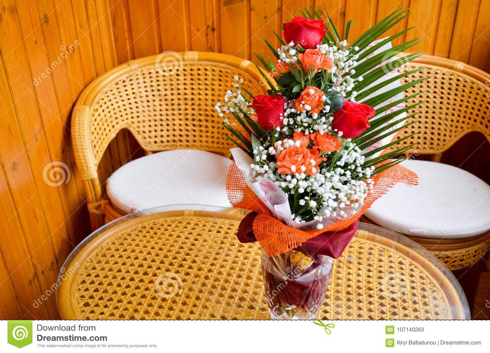 Rode en gele rozen in een boeket met gestrooide witte bloemen op een lijst