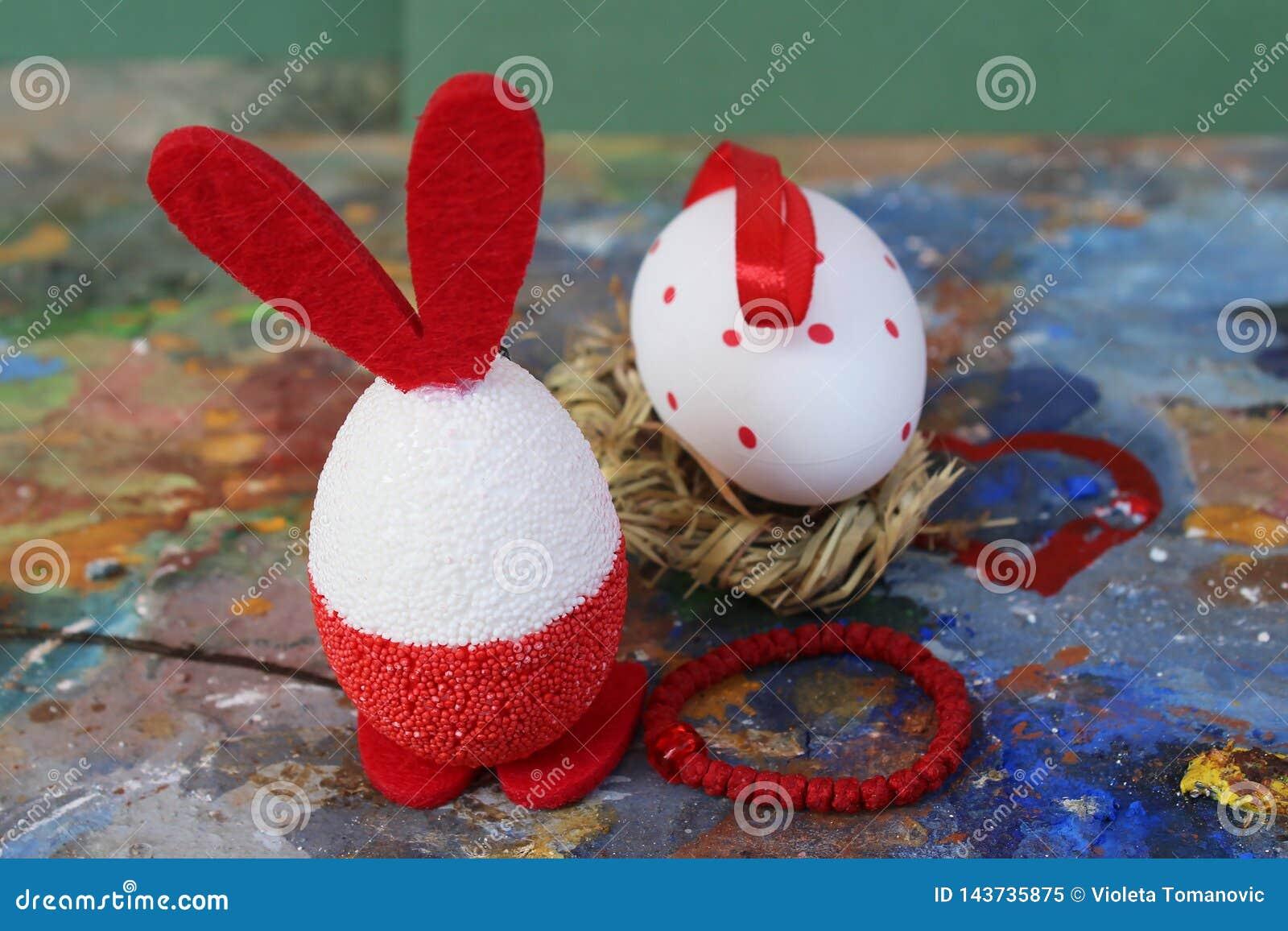 Rode en witte het konijntjeseieren van Pasen op oud kleurrijk artistiek houten palet