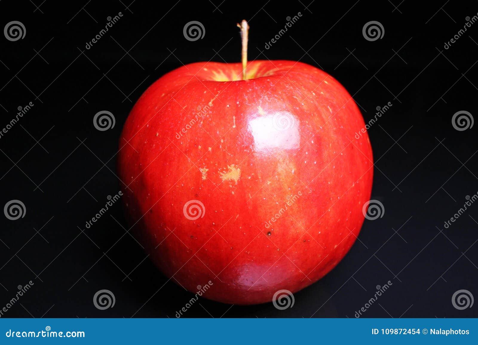 Rode glanzende gehele appel op zwarte weerspiegelende studioachtergrond Geïsoleerde zwarte glanzende spiegel weerspiegelde achter