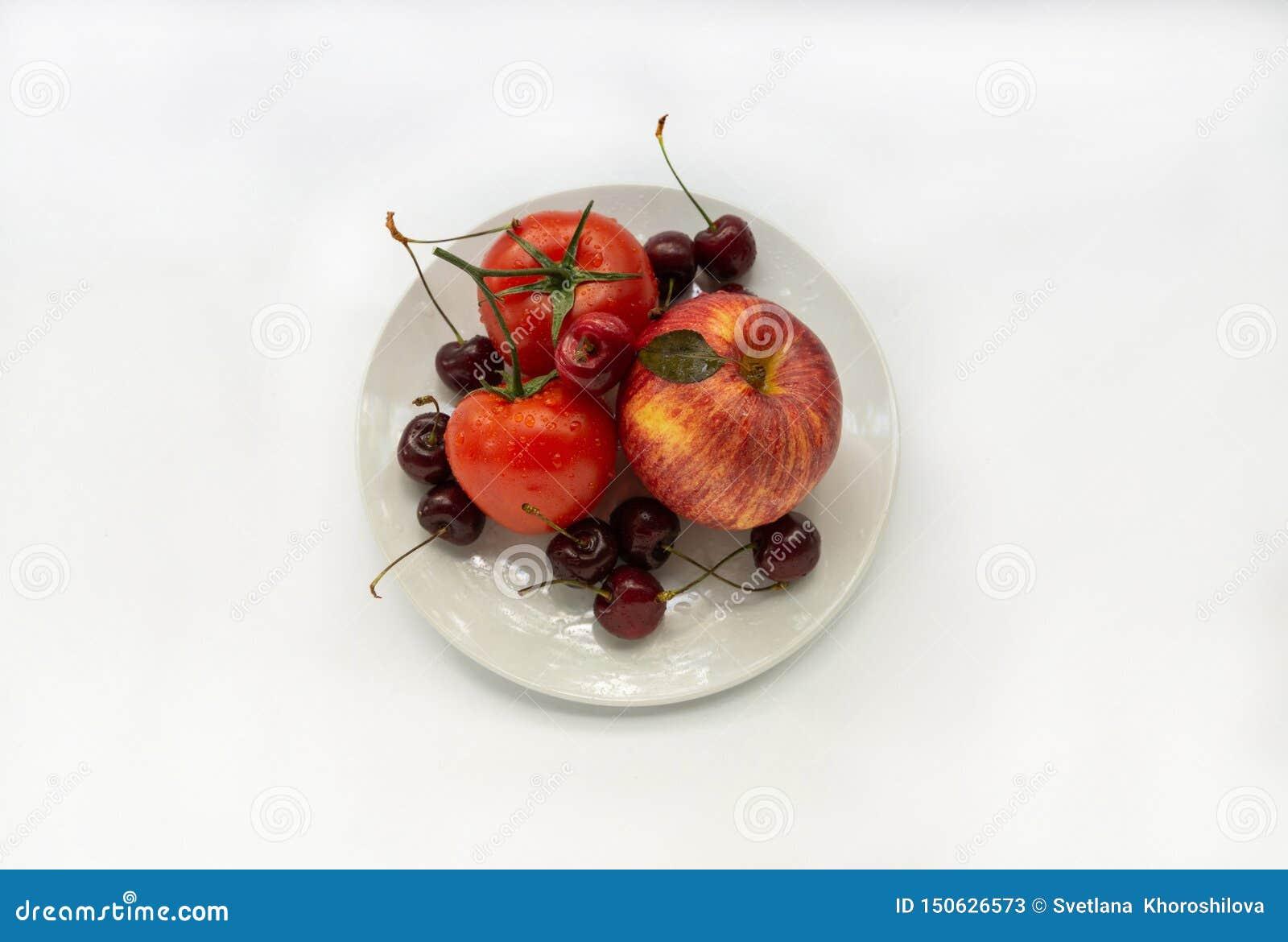Rode groenten en vruchten op een witte plaat