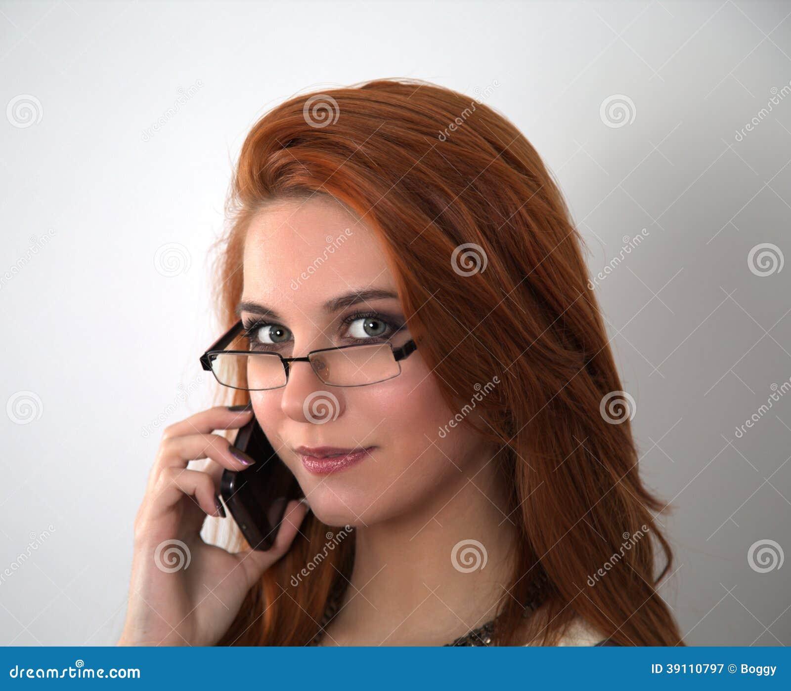 Rode haarvrouw met mobiele telefoon
