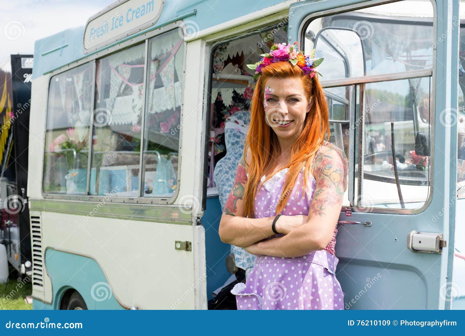Rode haired dame die zich met uitstekende roomijsvrachtwagen bevinden
